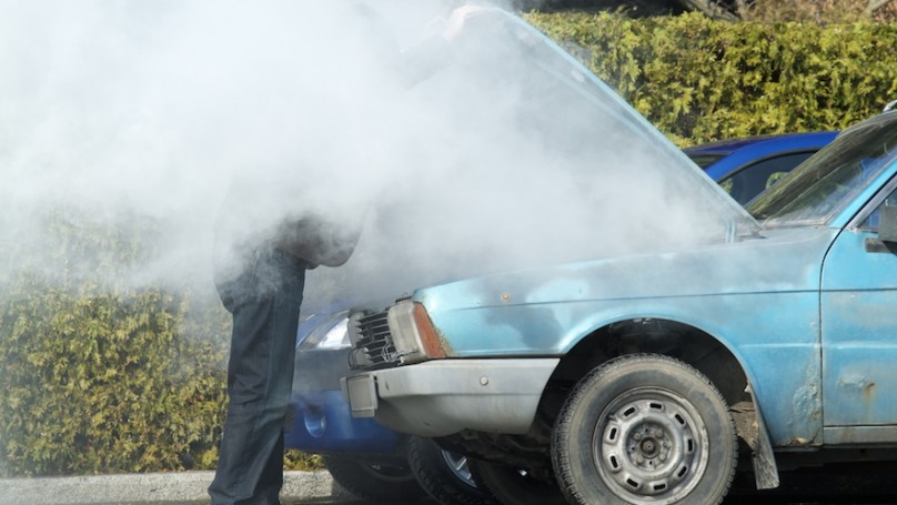 Man looking at a smoking engine in his car