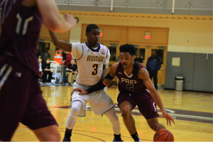 St. Joe's Prep's Darius Kinnel drives to the hoop with Roman's JP Sanders right behind him. (Photo by: Anthony Simuro)