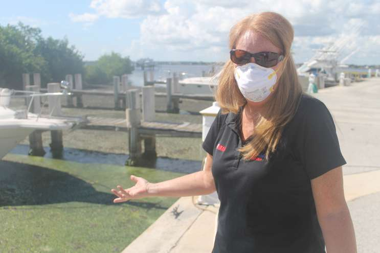 For Mary Radabaugh of Central Marine a paper mask offers little relief from the algae's pungent smell. Photo by Amy Green