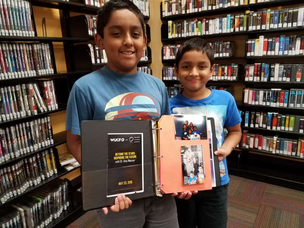 Brothers Isaac and Jacob Matthew show off a photo album of STEM related activities they've participated in with the Orange County Library System. Photo: Brendan Byrne