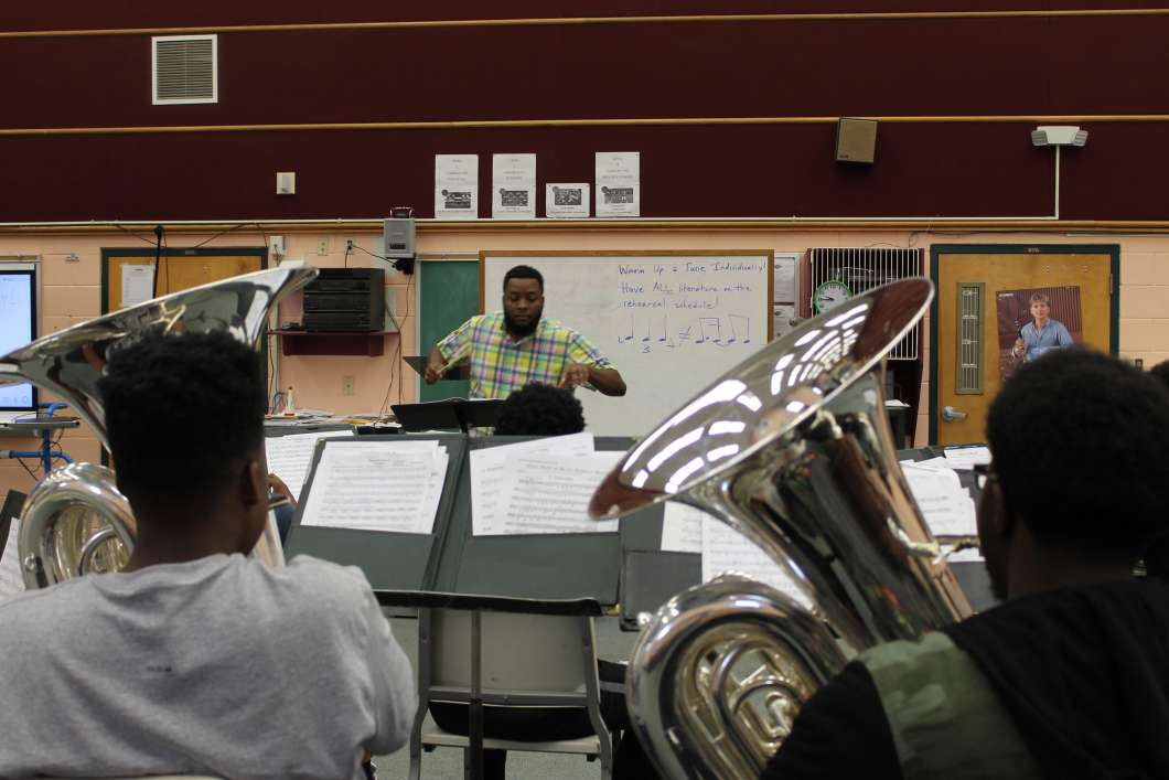 Jamaal Nicholas conducts the brass section of the Jones High School marching band. Photo: Matthew Peddie, WMFE