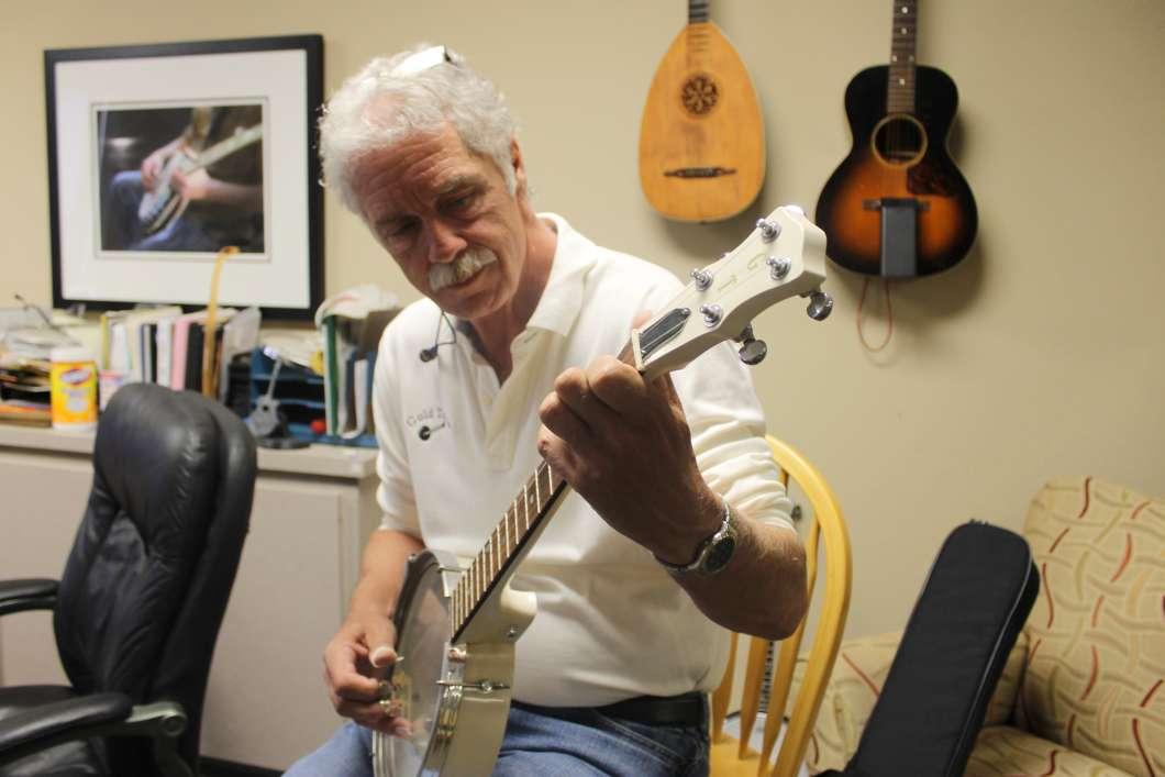 Gold Tone founder Wayne Rogers plays one of his banjos. Photo: Matthew Peddie, WMFE.