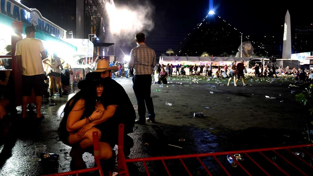 People take cover at the Route 91 Harvest country music festival after a gunman opened fire on the festival from a room in the Mandalay Bay Resort and Casino in Las Vegas, Nevada. Photo courtesy NPR