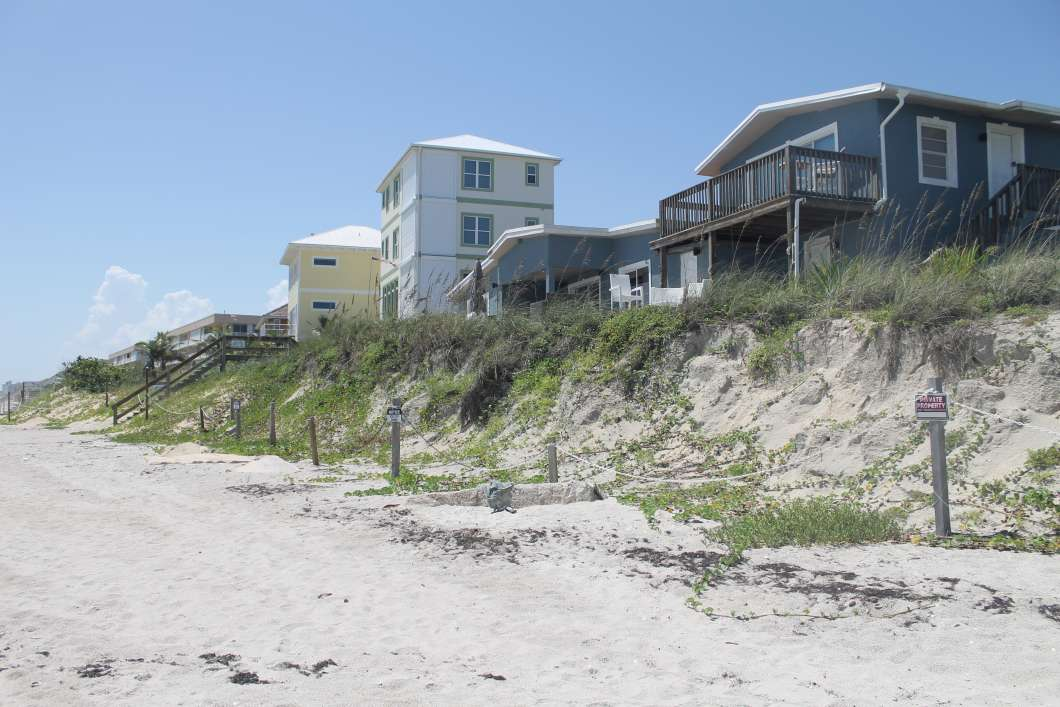 Homes perch atop a sand dune, left exposed after a series of storms and hurricanes washed away a sea wall. Photo by Amy Green