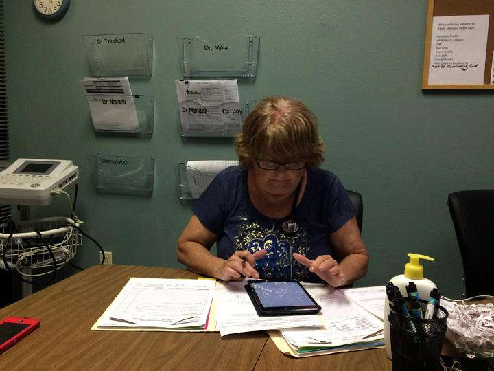 Donna Armes, director of The Haley Center in Winter Haven works on a patient's chart. (Julio Ochoa, WUSF)