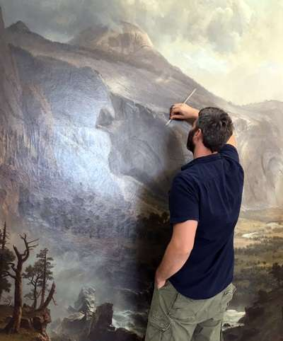 Image: A conservator at ArtCare Conservation Studio in Miami works to remove old varnish and grime from Albert Bierstadt's 1867 painting The Domes of the Yosemite, morsemuseum.org