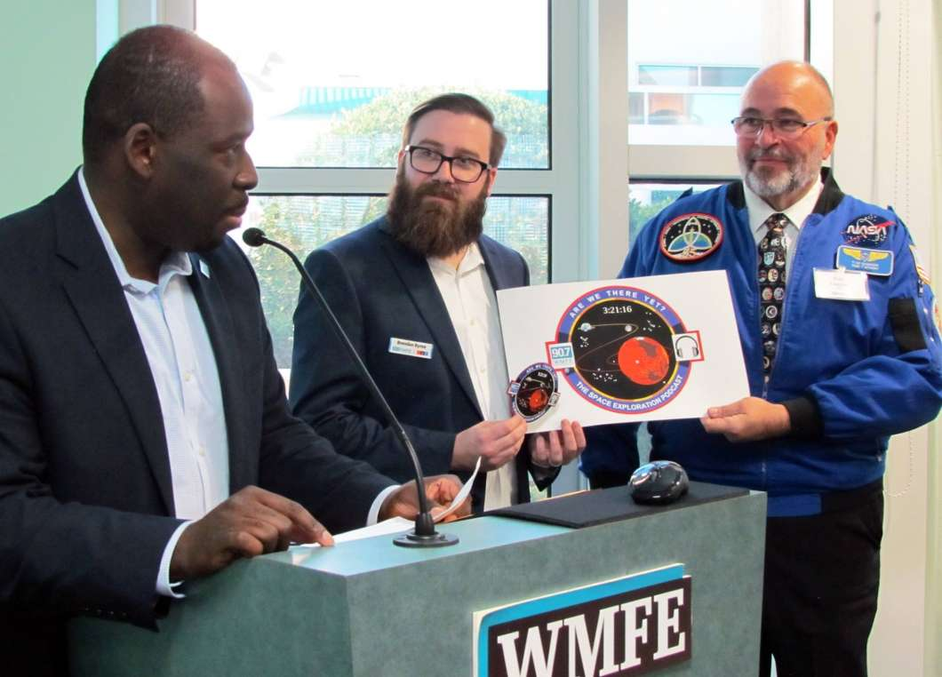(L to R) WMFE's President and General Manager, LaFontaine Oliver, WMFE's Brendan Byrne and Designer Tim Gagnon unveil Are We There Yet?'s first mission patch. Photo: WMFE / Jenny Babcock