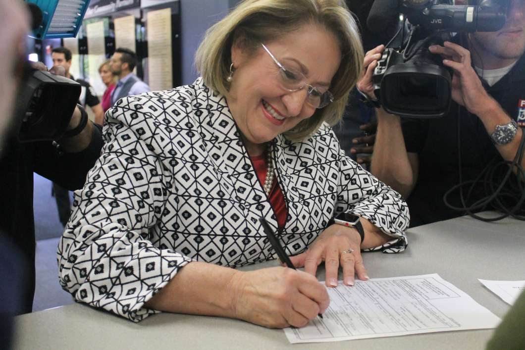 Orange County Mayor Teresa Jacobs signs paperwork for her run to be county school board chairwoman. Photo by Amy Green