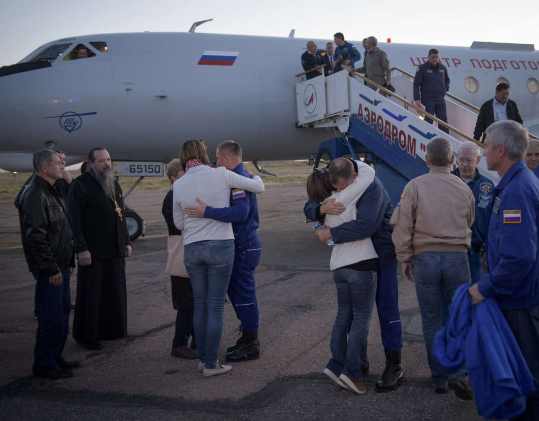 Expedition 57 Flight Engineer Alexey Ovchinin of Roscosmos, left, and Flight Engineer Nick Hague of NASA, right. embrace their families after landing at the Krayniy Airport, Thursday, Oct. 11, 2018 in Baikonur, Kazakhstan. Photo: NASA