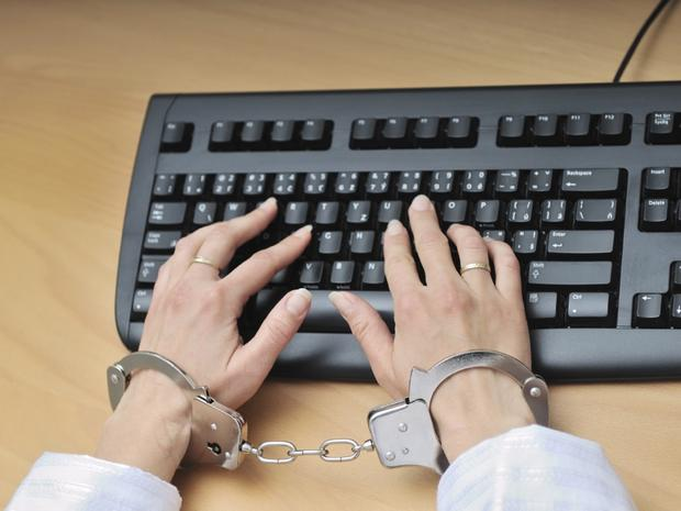 Hands tied with handcuffs typing on keyboard - crime or workaholic concept.