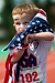 Carson Cooper, 4, of Warren, Mich., wraps himself in the American flag after placing in a track event, Saturday, Aug. 3, 2013, in East Lansing, Mich.