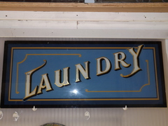 Ornate hand painted glass laundry sign