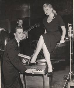 Cy, with an unknown performer, demonstrates his prowess on a toy piano at the Raleigh Room in New York City.