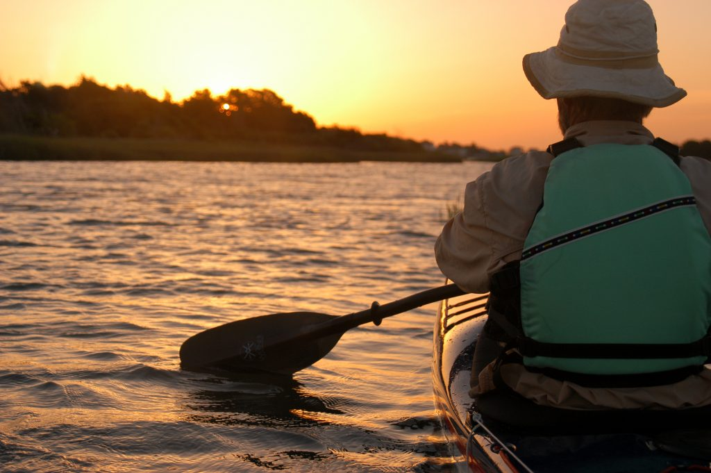 Sea kayaker paddling into the sunrise.
