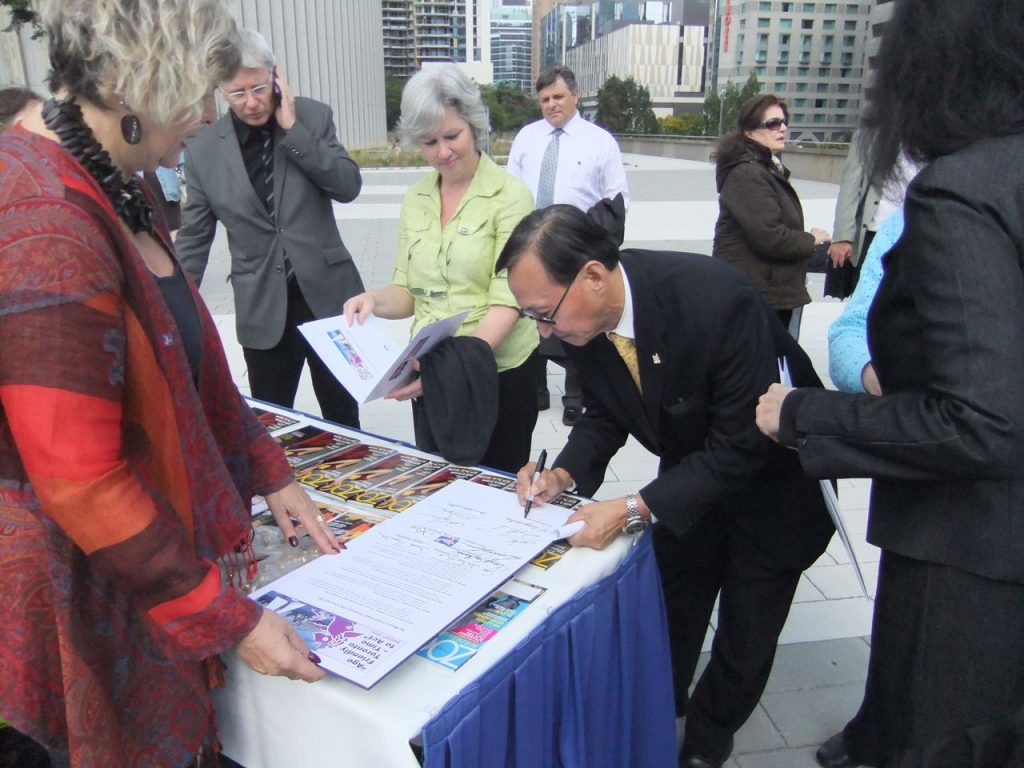 Toronto CARP Chapter Chair Adina Lebo looks on as Toronto City Councillor Raymond Cho signs the pledge