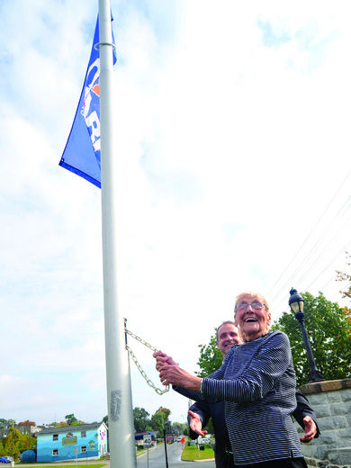 89-year-old Doris McEwan celebrates as she raises a flag to commemorate National Seniors Day as Brockville mayor David Henderson looks on