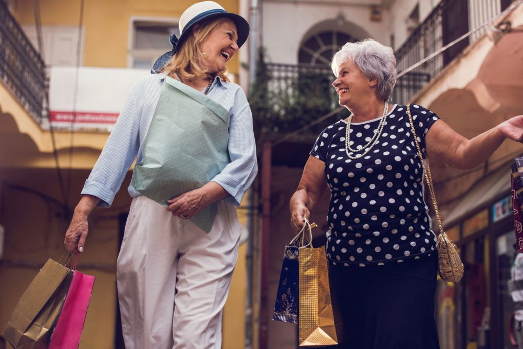 Cheerful old women communicating during a shopping day and having fun.