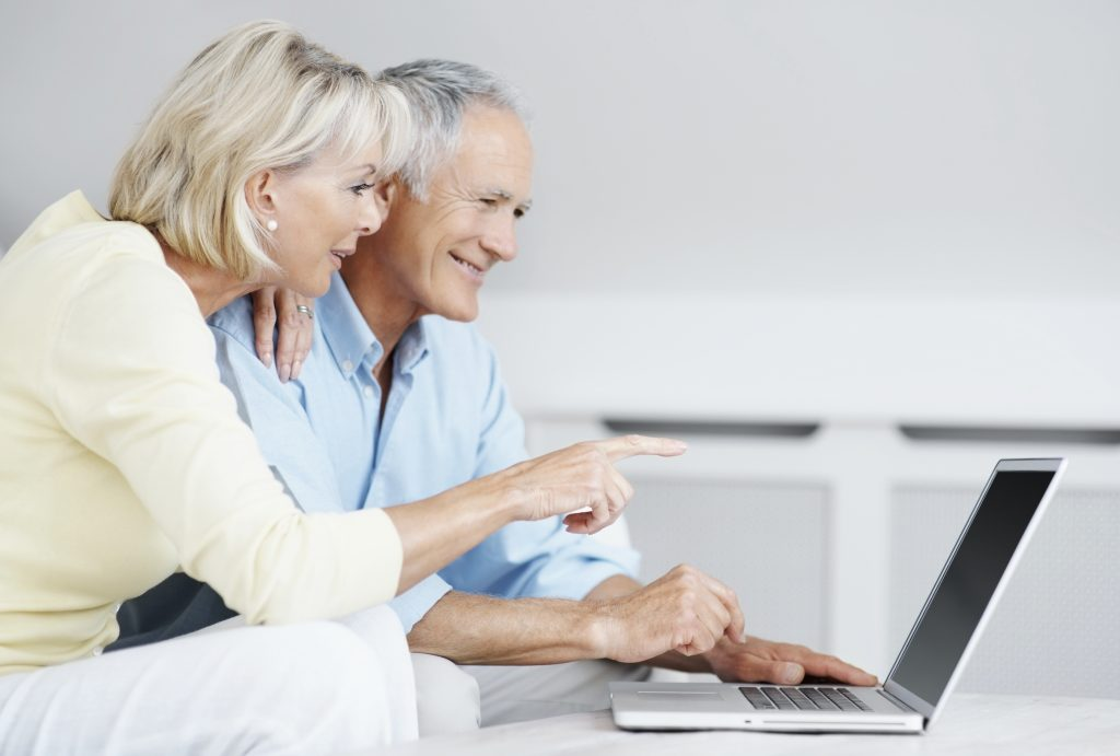 Portrait of a smiling senior man with mature woman pointing at laptop screen