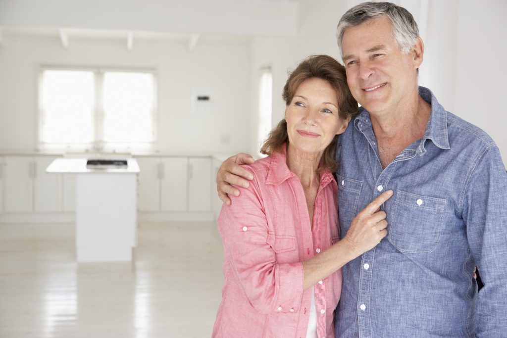 Senior couple standing in empty new home