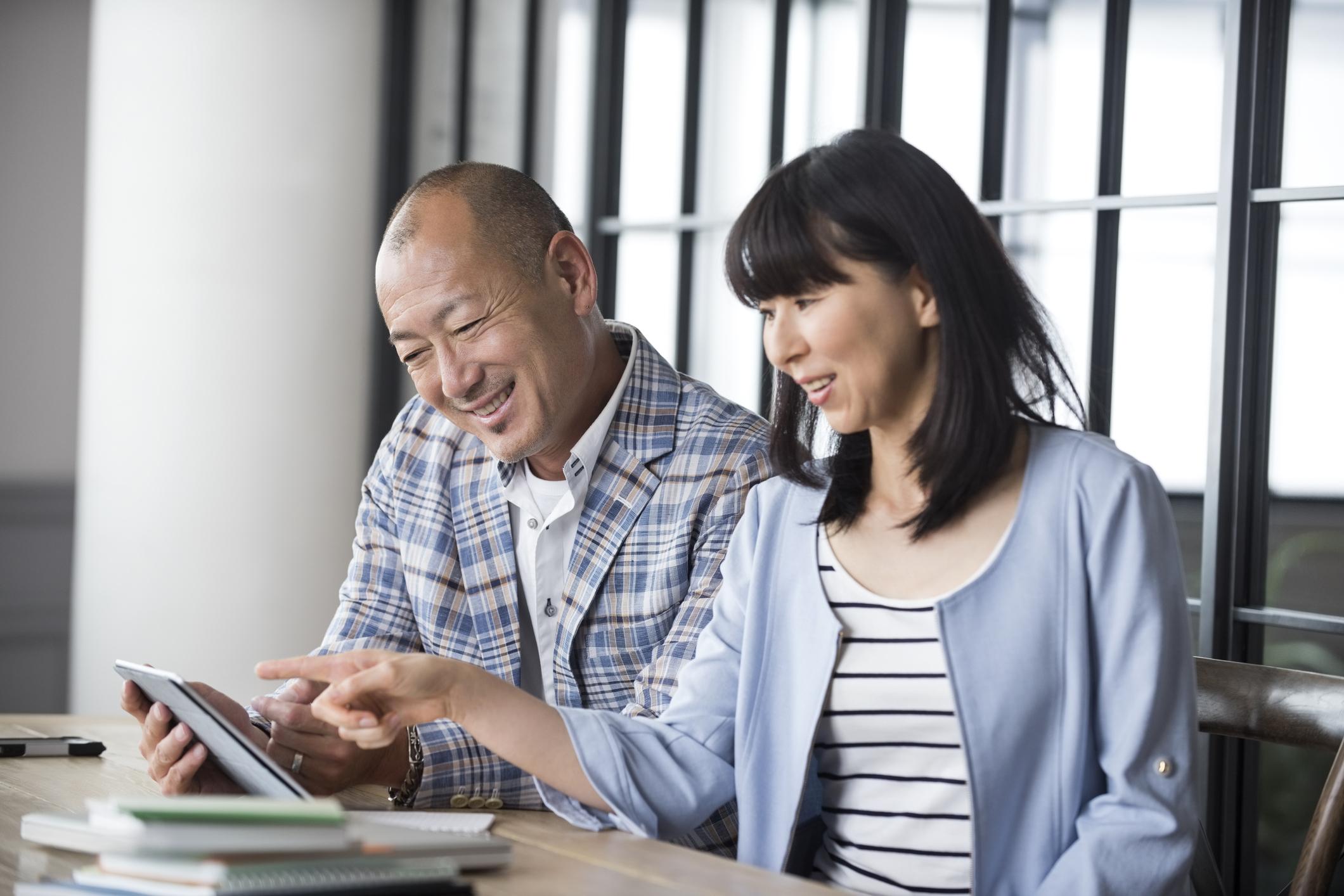 Mature Japanese businessman looking at digital tablet. Asian man and woman looking at digital tablet.