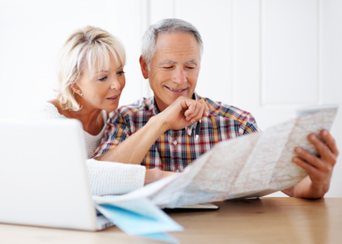 Portrait of a loving couple planning vacation with map and laptop