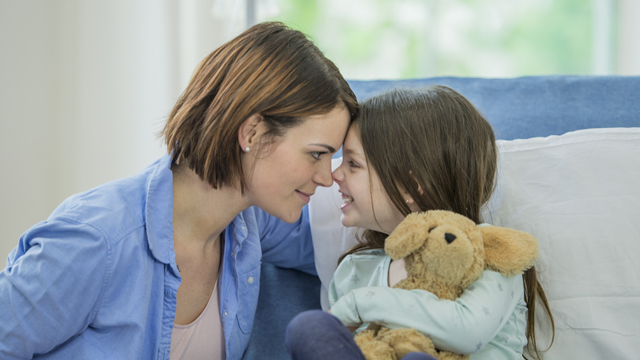 A young Caucasian girl is indoors in a hospital room. She is wearing casual clothing. She is lying in bed and holding a stuffed dog. She is rubbing noses with her mother.