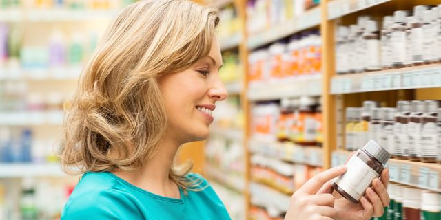 Pretty mid adult woman reading instructions on pill bottle while standing by shelf at pharmacy store. Horizontal shot.