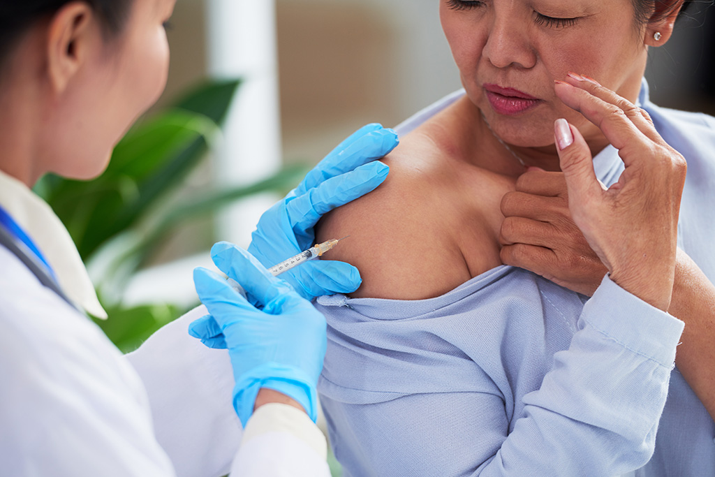 An older adult is getting vaccinations in her upper right shoulder.
