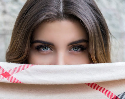 A brunette woman peering over a piece of fabric that covering her face from the bridge of the nose down.