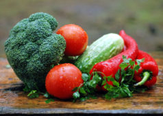 Broccoli, red peppers, tomatoes and cucumber bunched together on a cutting board.