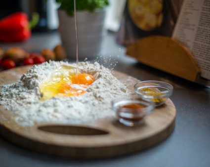 An egg cracked in flour on a cutting board with a cookbook in the background.