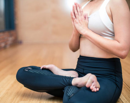 Woman sitting cross-legged with her palms together in a yoga studio.