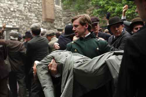 Downton Abbey S1E6: Branson carries injured Lady Sybil away from the unruly crowd at the counting of the vote