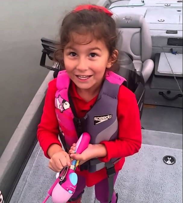 Super Dad cheers on daughter as she fishes up a huge bass with her Barbie fishing pole