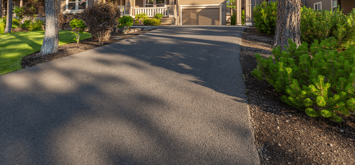 A residential asphalt driveway without borders and needs sealing.