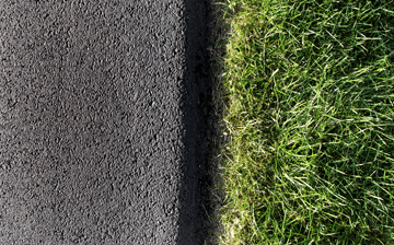 The edge of an asphalt driveway next to grass