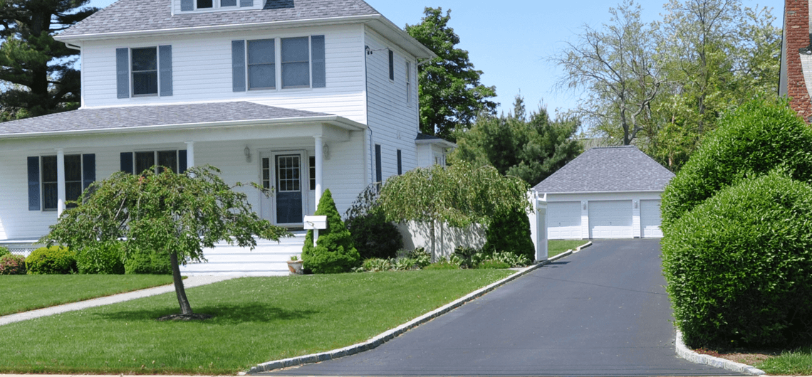 A residential asphalt driveway with concrete borders