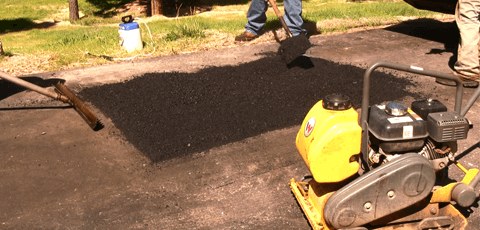 Asphalt repair contractors repairing and patching an asphalt driveway