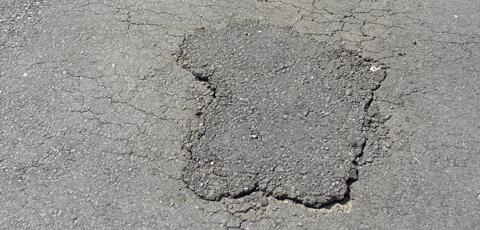 An asphalt skin patch on an asphalt driveway