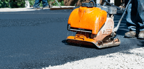 Compacting a freshly laid asphalt driveway with a plate compactor