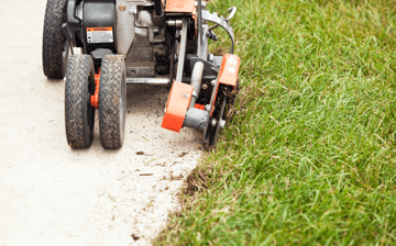 An edger edging a concrete driveway with grass