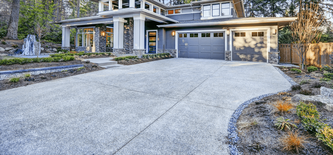 A new gray concrete driveway with gray rock border