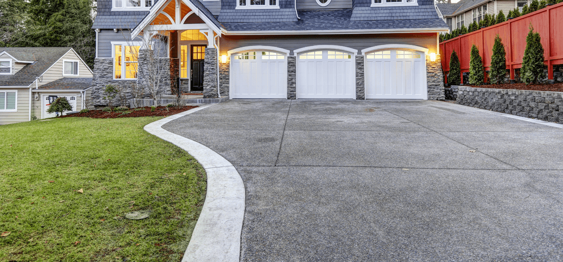 A newly poured dark gray driveway with light gray borders