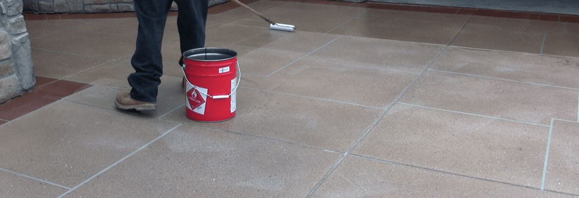 A concrete driveway with an overlay being sealed with a roller