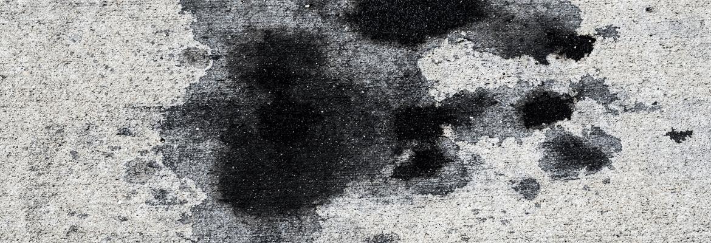 A concrete driveway with oil spots
