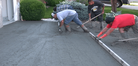 Concrete contractors pouring and finishing a concrete driveway