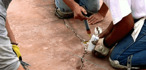 A contractor performing concrete crack repair before an overlay
