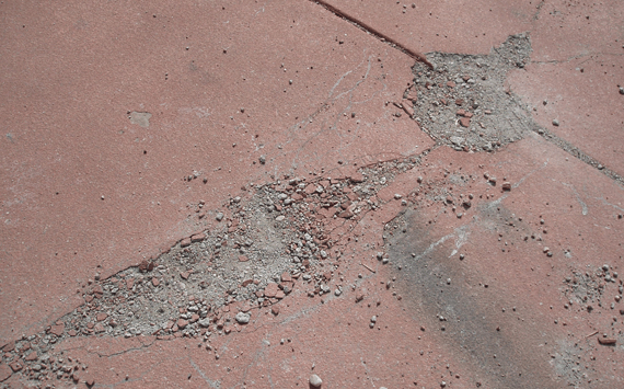 A poorly repaired concrete repair on a residential concrete driveway