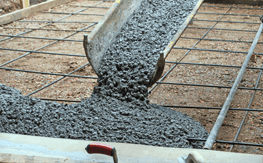 A concrete chute with concrete being poured out of it