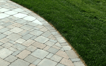 The edge of an interlocking paver driveway next to grass